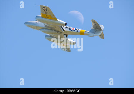 Gloster Meteor fighter jet plane flying past the moon in blue sky. Early jet fighter, Meteor T7 WA591 restored. RAF first jet. Space for copy - Stock Image