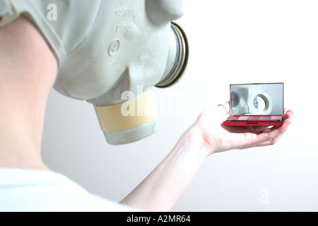 Someone in a gasmask looking at themself with a compact. - Stock Image