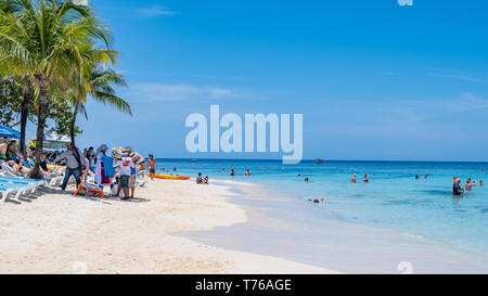 People on the beach at West Bay Roatan Honduras on a sunny April Day. - Stock Image