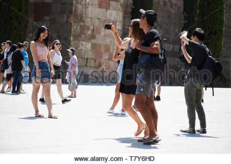 Tourists taking photographs and selfies on  Street in the City of Barcelona in Catalunya in Spain in Europe - Stock Image