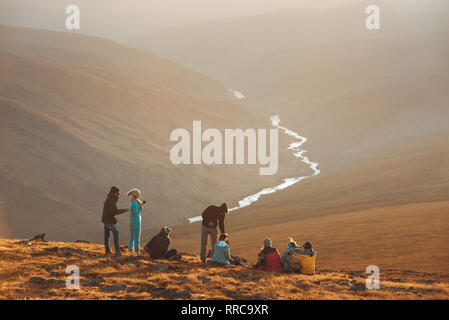 Big group of friends peoples relax on mountain top and looks at sunset - Stock Image