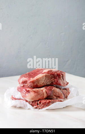 Three raw uncooked beef steaks in stack on crumpled paper on white marble table. - Stock Image