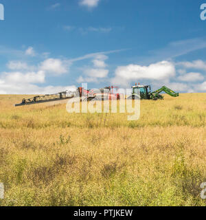 Farm tractor towing crop spraying unit in summer field - Stock Image