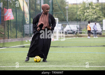 A Muslim woman dribbles a football on an astroturf pitch, dressed modestly with a hijab. - Stock Image