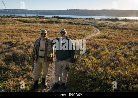 A portrait of two fly fisherman on a well worn trail to a salt water beach in northwest Washington State, USA - Stock Image