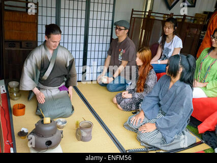Tea ceremony demonstration, on tatami mats and with traditional equipment used for cha-no-yu. Traditional costumes, - Stock Image