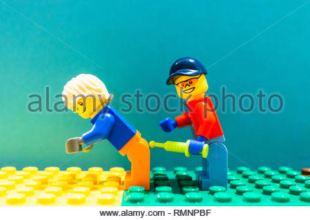 Poznan, Poland - February 13, 2019: Lego medical helper giving man a injection with a syringe in the back. - Stock Image