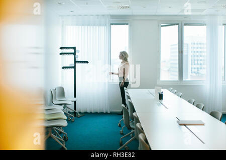 Woman standing in board room - Stock Image