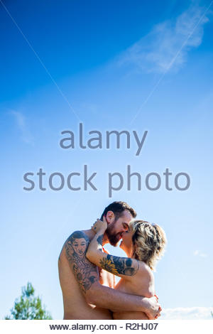 Young heterosexual couple poses naked in nature - Stock Image