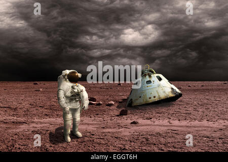 An astronaut surveys his situation after being marooned on a barren planet. Ominous clouds form in the distance - Stock Image