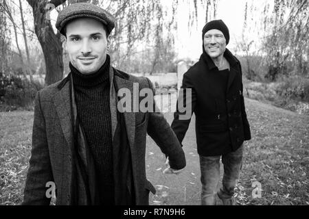 Black and white portrait of male gay couple holding hands and smiling as they walk on park pathway - Stock Image