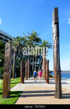 Pedestrians walking amongst totems depicting past Aboriginal life in the area, Marlin Wharf, Cairns, Far North Queensland, FNQ, QLD, Australia - Stock Image