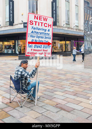 East Asian man seated at a pedestrianised junction in Middlesbrough Town Centre holding an advertising placard for New Stitch a Turkish Tailor shop - Stock Image