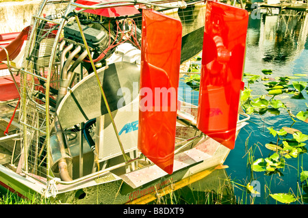 Airboat closeup mechanical details vertical red rudders airplane-style propeller protected by metal cage - Stock Image
