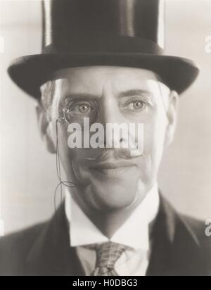Portrait of man wearing monocle and top hat - Stock Image