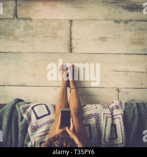 Woman lying on the couch with legs resting on the wall relaxed looking at the phone - concept of girl alone at home with technology - desaturated vint - Stock Image