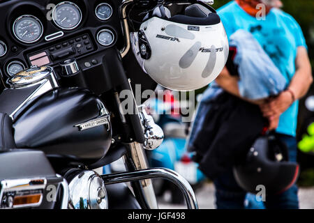 White helmet hanging on the handlebar of a Harley Davidson Electra Glide. - Stock Image