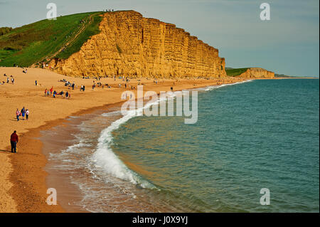 People on the beach at West Bay on the Jurassic Coast in Dorset under the towering East cliff. - Stock Image