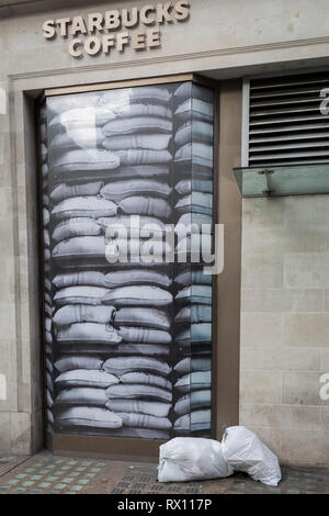 Plastic bags full of rubbish awaits collection outside a Starbucks window on the corner of Mortimer Street and Regent Street, on 4th March 2019, in London England. - Stock Image