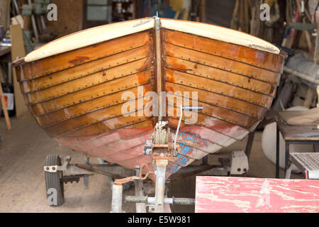 Wooden boat in for repair in boat shed. - Stock Image