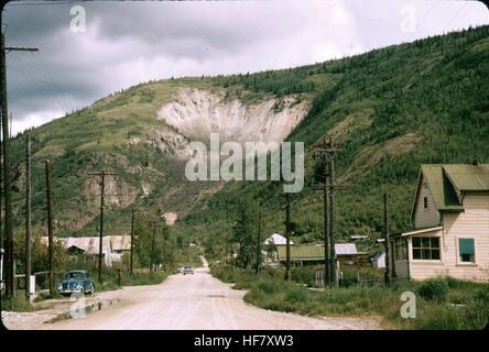 Streetscene and landslide at mountain side; Dawson, Yukon Territory, Canada. - Stock Image
