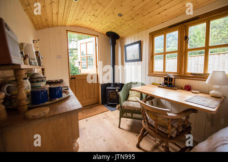 Interior of a cosy Shepherds Hut with a woodburner, bed and antique furniture all ready to let out to holidaymakers in Suffolk - Stock Image