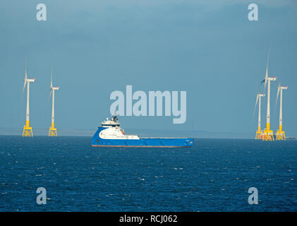 Aberdeen bay wind farm operational from May 2018 flanks the oil supply vessel NAO Prosper at anchor. - Stock Image