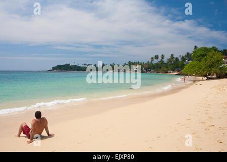 TOURIST SITTING ON UNAWATUNA BEACH - Stock Image