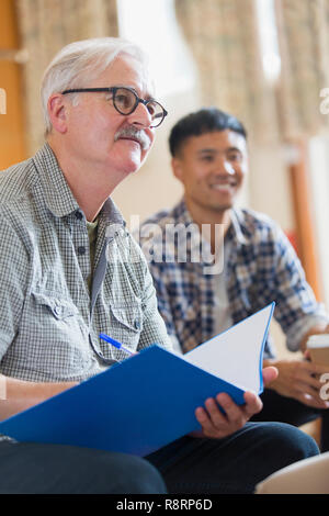 Attentive senior man taking notes in meeting - Stock Image