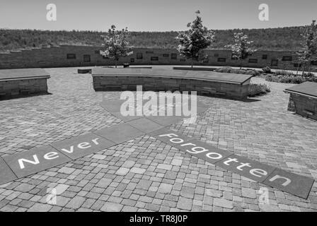 Entrance to Columbine High School Memorial showing the words, 'never forgotten' in foreground and display of plaques in distance in black and white. - Stock Image