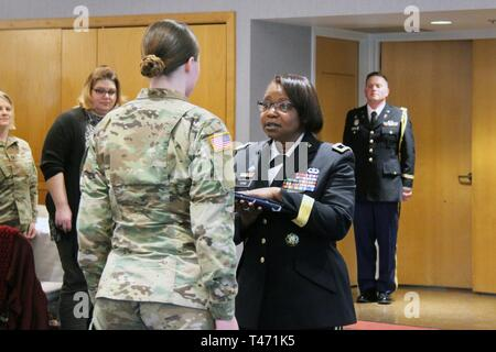 Brig. Gen. Twanda Young (right), deputy commanding general for the U.S. Army Human Resources Command, gives a flag to Sgt. Christine Meyers with the Fort McCoy Army Health Clinic during the Women's History Month observance March 14, 2019, at McCoy's Community Center. Young was the guest speaker. - Stock Image