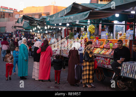 Marrakech lifestyle - local arab people buying food at a market stall in the evening, Djemaa el Fna square, Marrakesh medina, Marrakech Morocco Africa - Stock Image