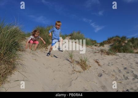 Two children enjoying themselves on the beach at Rømø, Denmark - Stock Image