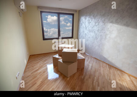 Renewed room with painted walls, varnished lacquered parquet and several carton boxes in the middle. - Stock Image