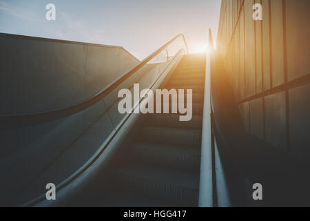 City outdoor grungy modern escalator goes up to sun and teal sky, rusty metal tiled wall on the right, view from - Stock Image