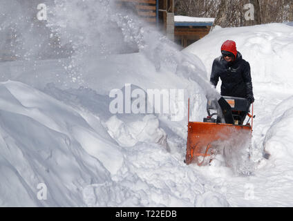 A woman using a snow blower to clear snow from her garden in Quebec. Winter 2018-2019 saw very heavy snowfall. - Stock Image