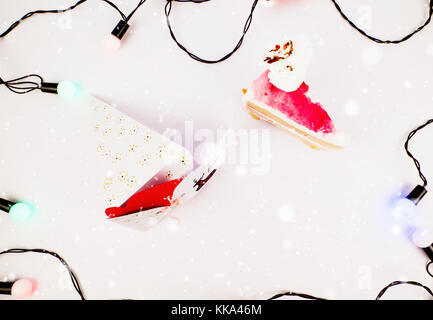 Christmas Decoration with Cake slice Gifts and Cake slice under snow with lights for best background image for Holiday - Stock Image