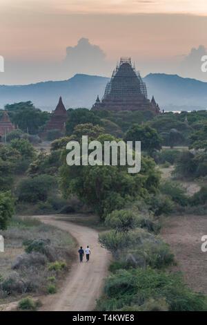 Two men walk the road to Old Bagan at sunset, Myanmar. - Stock Image