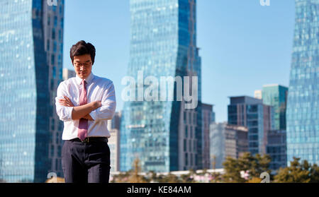 Businessman worried standing outdoors during daytime - Stock Image