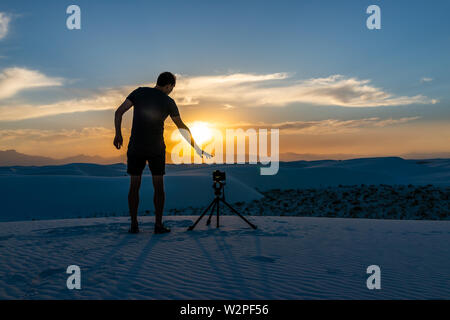 Man photographer with tripod doing time lapse photography with camera in white sands dunes national monument in New Mexico view of sunset - Stock Image