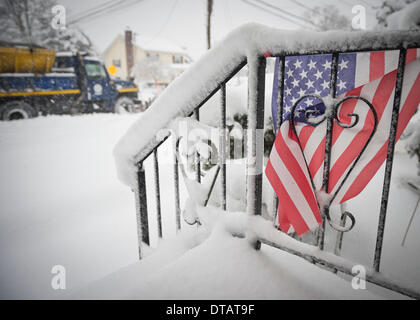 Merrick, New York, U.S. February 13, 2014 - As yet another snow storm slams into Long Island, a Town of Hempstead snow plow drives past a snowy American Flag decorating the front stoop railing of a home. New York's governor declared a state of emergency, and 5 to 14 inches of snow are expected to fall on Nassau and Suffolk Counties through to the evening, Credit:  Ann E Parry/Alamy Live News - Stock Image