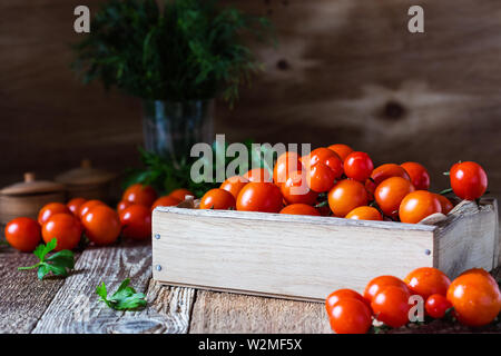 Crate of freshly picked organic red cherry  tomatoes on rustic wooden table, plant based food, close up, selective focus - Stock Image