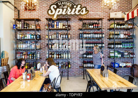Florida Babcock Ranch master planned community first solar-powered city Slater's Goods & Provisions market cafe woman eating shelves wine bottles liqu - Stock Image
