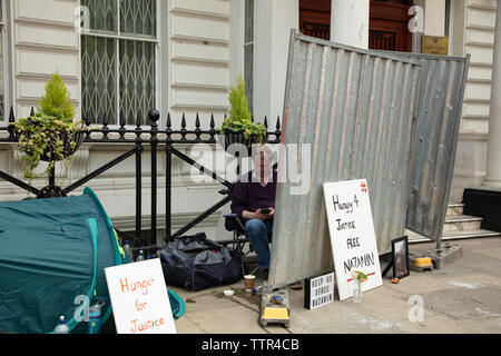 London, UK. 17th June 2019. Hunger striker Richard Ratcliffe behind an iron board, placed there by Iranian embassy staff and builders, in front of the Iranian embassy in London protesting the detention of his wife Nazanin Zgahari in Iran over spying allegations. Credit: Joe Kuis / Alamy - Stock Image