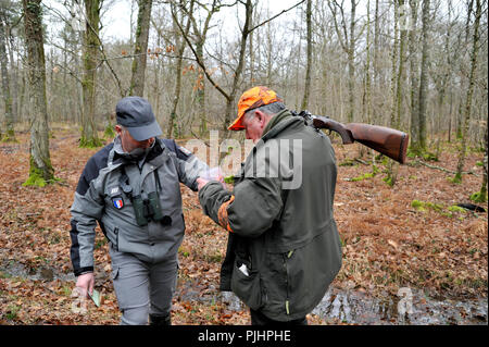 France, hunting and security, officer of French environmental policy controlling hunter during a hunt in Loire-Atlantique Department. - Stock Image