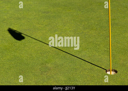 Close up of golf hole with shadow of flag on Green. - Stock Image
