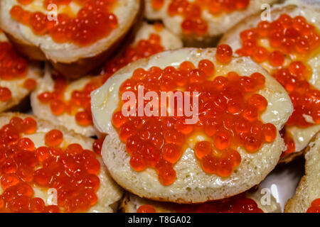 Sandwiches with butter and red caviar on a plate closeup - Stock Image