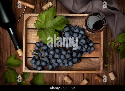wooden box with grapes and a glass of wine, a bottle of wine on the old wooden background. view from above - Stock Image