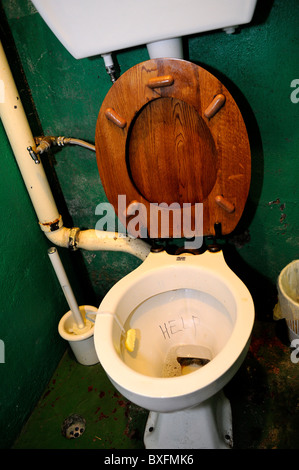 Old fashioned toilet with wooden seat, with 'Help' scribbled in bowl - Stock Image