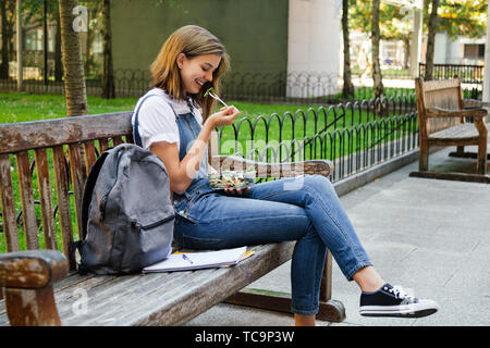 Student girl in denim overalls having healthy lunch while sitting in a bench outdoors - Stock Image